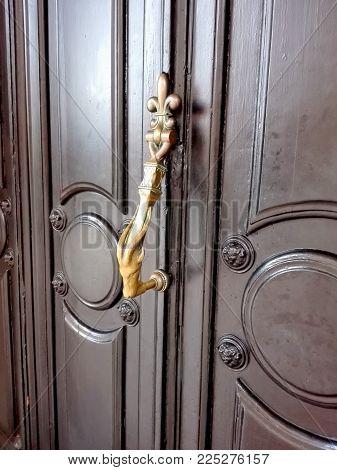 Beautiful doorknob. Wooden door with a metal door handles in the form of Aries.