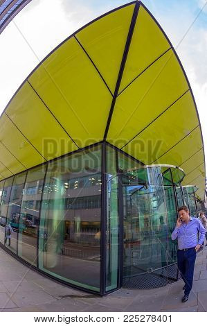 LONDON, ENGLAND - NOVEMBER 27, 2017: Wide angle shot of futuristic office building in Central London with a businessman in front talking on the phone.