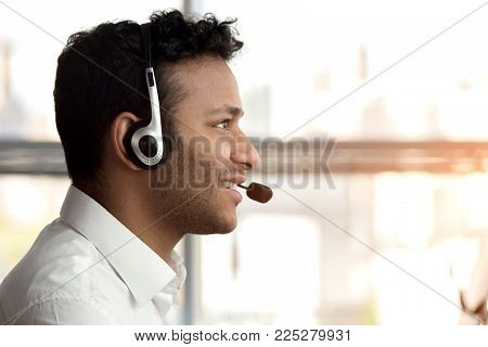 Side view stubbled black man with headset. Smiling black indian man with headset, close up.