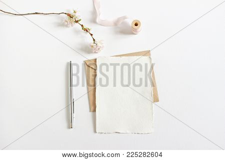 Wedding spring styled stock photo. Feminine desktop mockup with blossoming cherry tree branch, silver ballpoint pen, craft envelope and blank greeting card, white background. Empty space, top view.