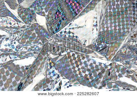 Holographic aluminium foil decor foil closeup pattern texture as background. Macro photo.