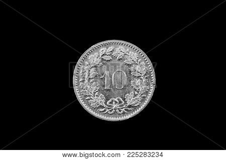 A Macro Image Of A Swiss 10 Centimes Coin Isolated On A Black Background