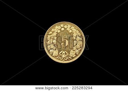 A Macro Image Of A Swiss 5 Centimes Coin Isolated On A Black Background