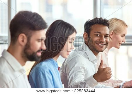 Sitting young indian black man showing thumb up. Young adult stubbled black man showing approval gesture, thumb up.