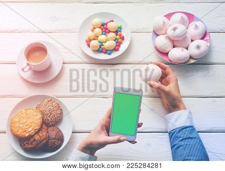 Girl blogger taking a food photo with smartphone camera. Clipping path.