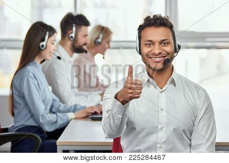 Cheerful american black operator with thumb up. Portrait of young male customer service representative, working co-workers background.