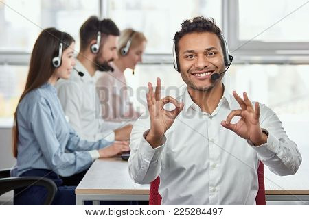 Happy call centre worker giving ok gestures. Portrait of handsome indian black man makes all right, OK, sign using both hands. Everything is fine.