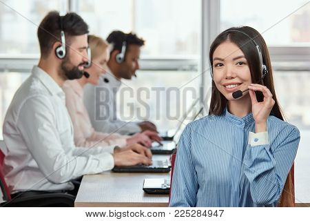 Korean girl wearing headset. Portrait of smiling girl adjusting headset in bright office.