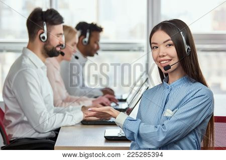 Asian girl pointng hand, working colleagues. Concept of smiling cheerful female operator recommend her colleagues as good workers.