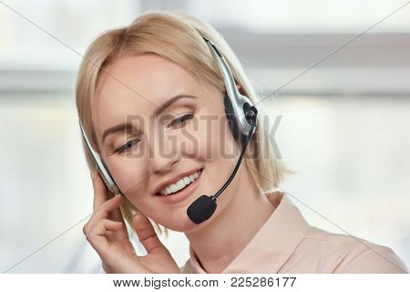 Bright picture of friendly female helpline operator. Beautiful business customer service woman - smiling at the office.