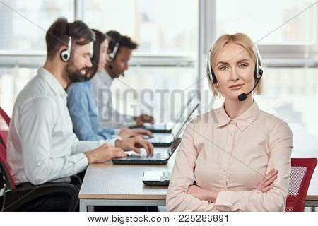 Female serious call center operator with folded arms. Blond mature woman with serious face. Bright windows background.