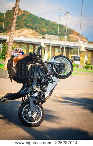 stuntrading on motorcycle stunts while driving on the rear wheel of a Willie stoppix stunt-riding on a sportbike