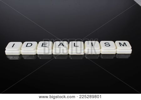 Idealism text word title caption label cover backdrop background. Alphabet letter toy blocks on black reflective background. White alphabetical letters..