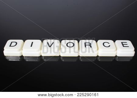Divorce text word title caption label cover backdrop background. Alphabet letter toy blocks on black reflective background. White alphabetical letters. Divorce.