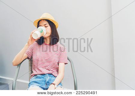 Bangkok, Thailand - February 06, 2018 : Woman drinking Starbucks coffee on the chair, Starbucks brand is one of the leaders in coffee service worldwide.