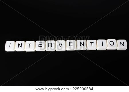 Intervention text word title caption label cover backdrop background. Alphabet letter toy blocks on black reflective background. White alphabetical letters..