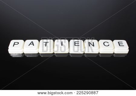 Patience text word title caption label cover backdrop background. Alphabet letter toy blocks on black reflective background. White alphabetical letters..