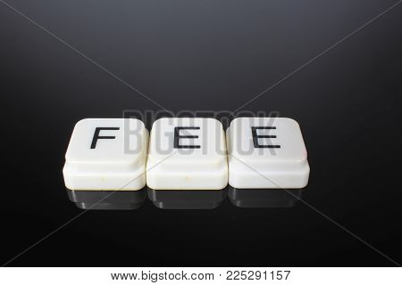 Fee text word title caption label cover backdrop background. Alphabet letter toy blocks on black reflective background. White alphabetical letters..