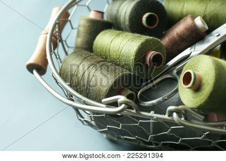Metal basket with color sewing threads on grey background, closeup