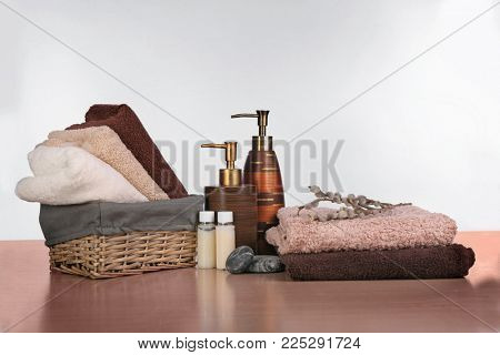 Wicker basket with set of fresh towels and toiletries on wooden table against white background