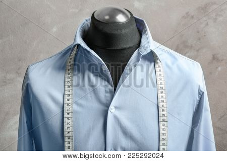 Shirt with measuring tape on tailor mannequin against light background
