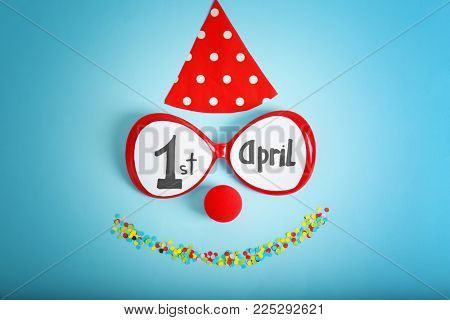 Clown nose, glasses and party cap on color background. April fool's day composition