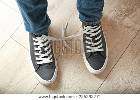 Man with shoelaces tied together. April fool's day prank