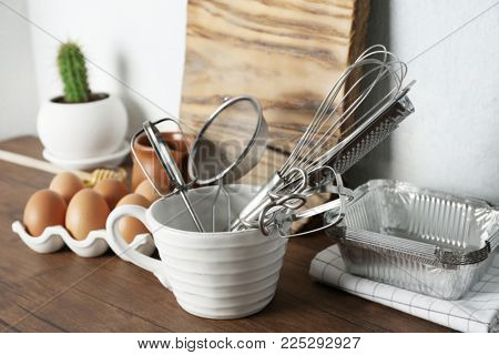 Cup with kitchen utensils and ingredients  for preparing pastries on table