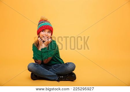 Pleased Young girl in sweater and hat sitting on the floor while reclines on her arms and looking away over orange background
