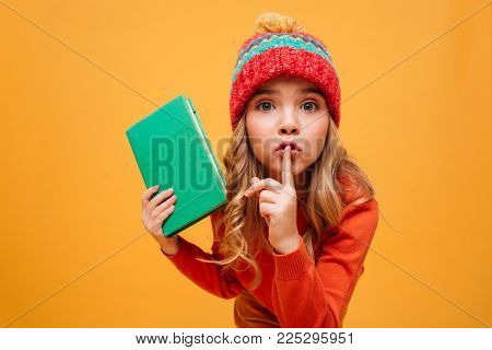 Enigmatic Young girl in sweater and hat holding book while showing silence gesture and looking at the camera