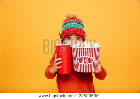 Scared Young girl in sweater and hat hiding behind the popcorn and plastic cup while looking at the camera over orange background