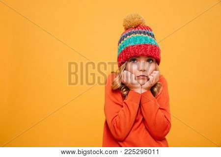 Bored Young girl in sweater and hat reclines on her arms and looking at the camera over orange background