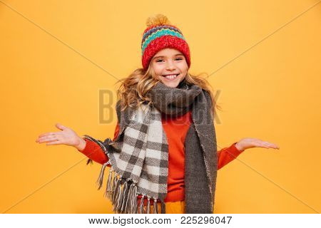 Happy Young girl in sweater, scarf and hat shrugs her shoulders while looking at the camera over orange background