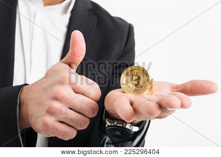 Close up of a man dressed in suit holding golden bitcoin on his palm and showing thumbs up gesture isolated over white background