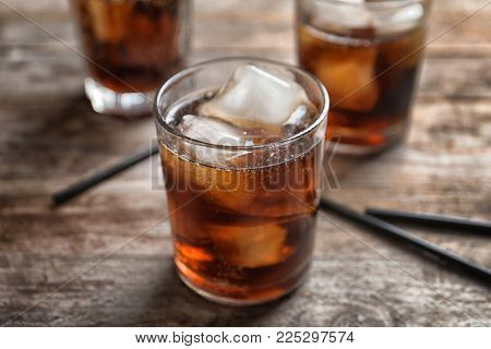 Glass of refreshing cola with ice on wooden table