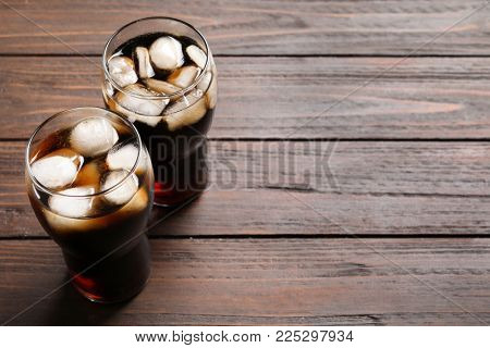 Two glasses of refreshing cola with ice on wooden table