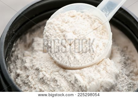 Measuring scoop and jar with protein powder, closeup