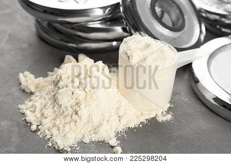 Protein powder and measuring scoop on table