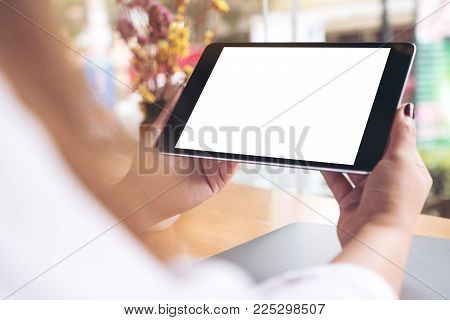 Mockup image of woman's hands holding black tablet pc with blank white desktop screen , laptop and coffee cup on wooden table in cafe
