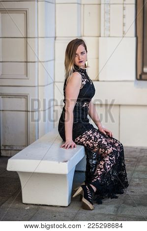 Elegant Young Woman In Sexy Black Lace Dress Looking Down Over Shoulder At White Stone Bench.