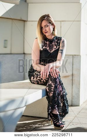 Eye Of Alternative Model Peeking From Blonde Hair While Seated On Bench Wearing Evening Gown Of Blac