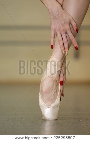 Leg of a ballerina in pointe. Beautiful graceful hands. Rehearsal dance on tiptoe. Close-up