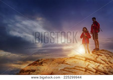 Silhouette of a champion couple on the top of a rock mountain view of sunset. Sport and active life concept.