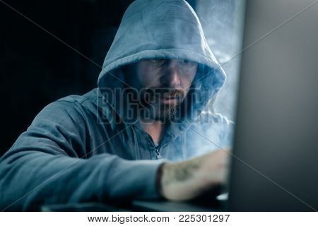 male hacker in a sweatshirt with a hood sitting and looking at the laptop in a dark room