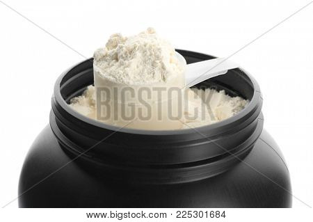 Measuring scoop and jar with protein powder on white background