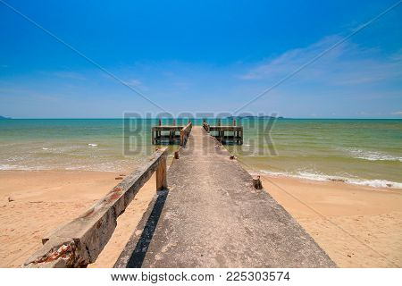 Concrete Bridge Extend The Sea Coast And Dry Water In Sunny On Blue Sky Background