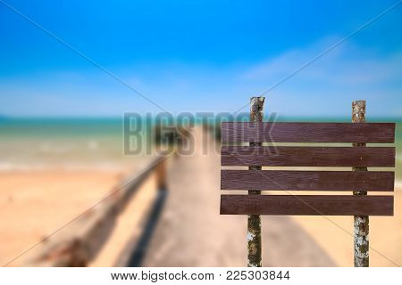 Brown Wooden Sing On Blurred Concrete Bridge Extend The Sea Coast And Dry Water Background