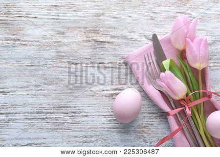 Beautifully decorated cutlery and eggs for Easter table setting on wooden background