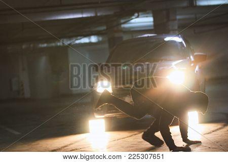 Man acrobat shows tricks somersault at underground parking, wide angle