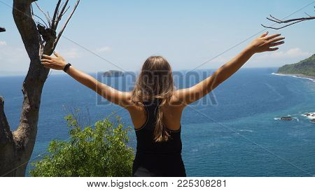 Young girl stands on the edge of a cliff and looks at the sea. Girl on the edge of the cliff enjoys the view of the ocean. Travel concept.